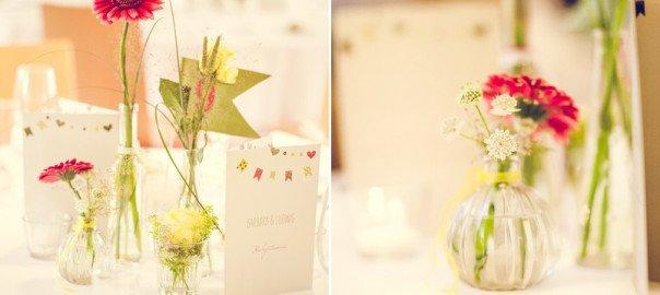 Inspiration für eine Tischdeko im Vintage-Stil mit kleinen Glasvasen und roten und gelben Blumen. Foto: Stefanie Danner.