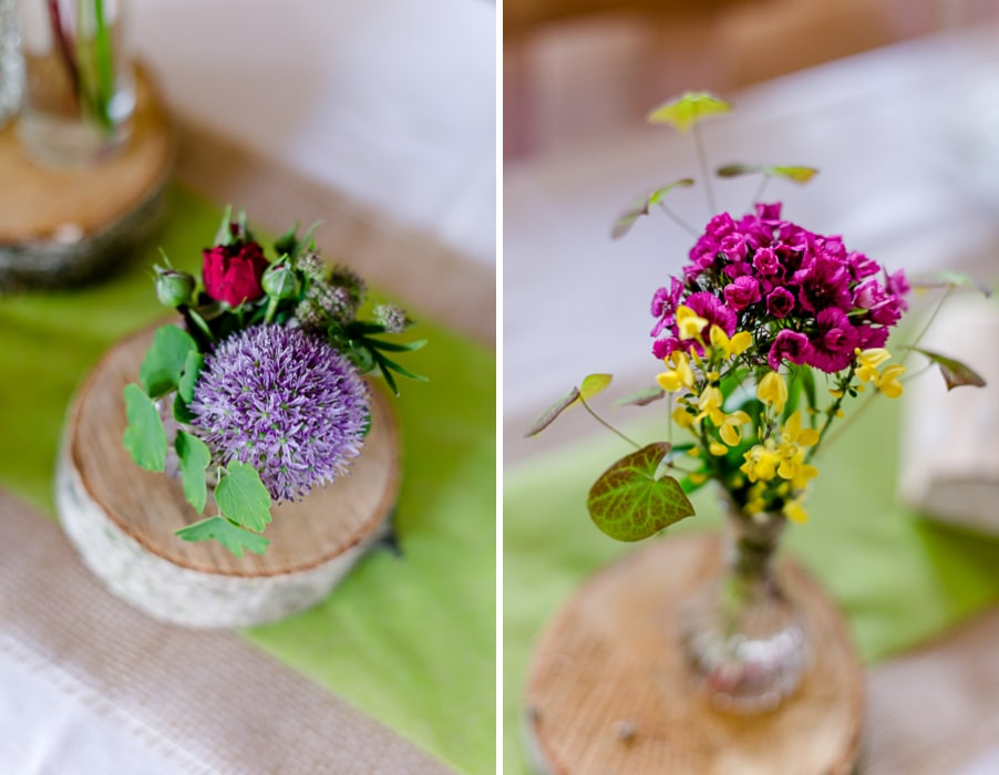 Bunte wilde Blumendeko mit Baumscheiben und Väschen bei einer Trachtenhochzeit