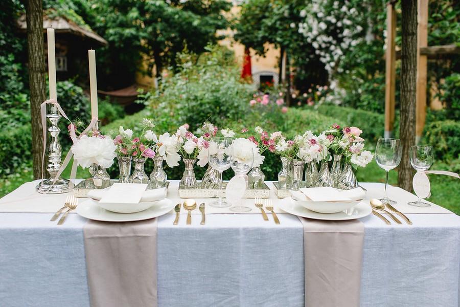 Hochzeits-Tischdeko mit kleinen Vasen und Spiegel-Tabletts in Weiß, Lila und Gold.