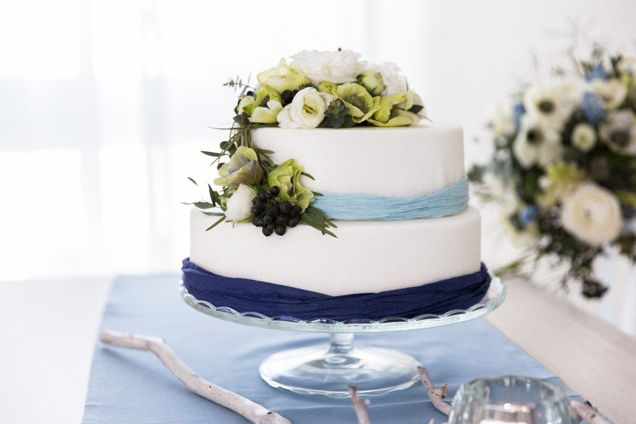 Kleine Hochzeitstorte passend zu einer Frühlingshochzeit in Blau, Weiß und grünen Blumen